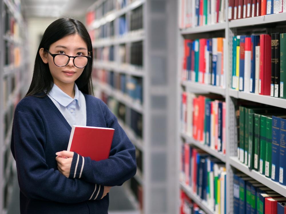 Junge Studentin mit Buch in der Bibliothek